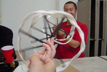 Graduate student Adam Feng plays with spiral-shaped Kinetic Sculpture